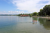 View from the harbor over Lake Constance to the pile dwellings Unteruhldingen, Baden-Württemberg, Germany