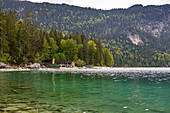 Blick über das türkise Wasser des Eibsee auf Wälder und Hütten am See, Grainau, Oberbayern, Deutschland