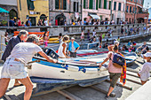 People pushing fishing boat into the sea, Vernazza, Cinque Terre, Liguria, Italy, Europe