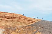 People walking around Gran Crater rim, Vulcano Island, Aeolian Islands, Sicily, Italy