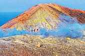 People walking on Gran Cratere rim, Vulcano Island, Aeolian Islands, Sicily, Italy