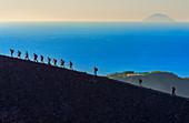Hikers walking around Gran Crater rim, Vulcano Island, Aeolian Islands, Sicily, Italy
