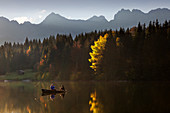 Angler in a rowboat on the Geroldsee in autumn, view to the Karwendel, Werdenfelser Land, Bavaria, Germany