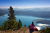 Woman takes a break from hiking, view from Herzogstand over Walchensee to the mountain range of the Alps, Bavaria, Germany