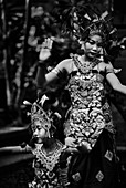 Two young Balinese girls perform a traditional dance in costume at their family compound in Ubud Bali Indonesia.