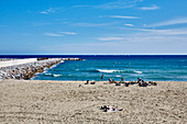 A wide view of the breakwater and people on the beach at Barceloneta, Barcelona, Catalonia Spain