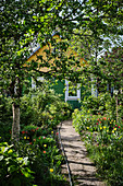A pathway leads to a cottage in a spring time garden in the Grodno region of rural Belarus.