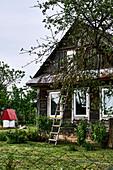 Leiter lehnt an traditionelles Holzhaus in einem kleinen Dorf in der Region Grodno, Weißrussland