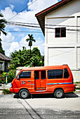 A small orange taxi parked on the side of the road in a street in Palangkaraya, Central Kalimantan, Borneo Indonesia.
