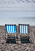Deck chairs on Brighton Beach on a spring day, Brighton, East Sussex, UK.