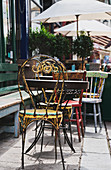 Distressed and weathered tables and chairs at a cafe in Old Town, Hastings, East Sussex UK.
