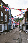 A street view of Courthouse Street decorated wtih bunting for the Jack In the Green festival, in Old Town, Hastings, East Sussex, UK.