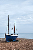 A traditional fishing boat sits on the pebbled sea shore of Rock A Nore beach looking out to the English Channel, Hastings, East Sussex, UK.