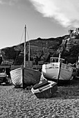 A traditional wooden fishing boats sit on the pebbled sea shore of Rock A Nore beach at with sandstone cliffs and funicular railway in the background, Hastings, East Sussex, UK.