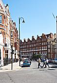 Men cross the road in a street in Kensington on a sunny day, London UK.