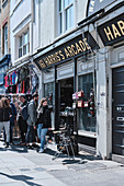Streetscape of a camera shop and people on Portobello Road, Notting Hill, London UK