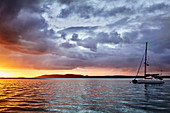 Sunset at Nelson Bay, New South Wales, Australia with a storm rolling in and a boat moored on the water