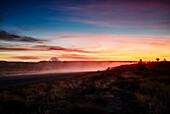 A dust trail from a truck at sunset along the Gibb River Road, Kununurra, The Kimberley, Western Australia, Australia.