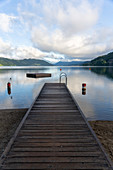 View over Lake Millstatt from the beach on the east bank of the alpine mountain and cultural landscape, Döbriach, Carinthia; Austria, Europe.
