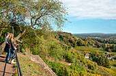 2 young women enjoy the view over Radebeul vineyards in autumn, Saxony, Germany