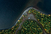 Camping in a VW bus on the lonely shore of a lake on Wilderness Road in Northern Sweden, forest from above