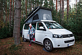 Woman at Vanlife Camping with VW bus in the forest in Sweden, Lake Siljan