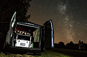 View into a camper van at night under the starry sky