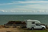 Ford Geländewagen mit Aufsetzkabine auf einem einsamen Stellplatz direkt am Meer, Ardmore, County Waterford, Irland