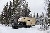 Van on snowy road in the forest in winter, near Arvidsjaur, Lapland, Sweden