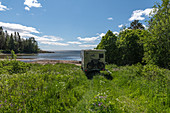 A van in the middle of a flower meadow by the sea, Lövudden, Västernorrland, Sweden