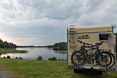 Van overlooking a deserted lake in summer, Högsäter, Västra Götaland, Sweden