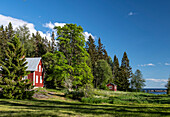 A typical, red wooden house in the forest with a view of the sea, Avikebruk, Västernorrland, Sweden