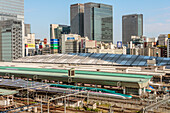 View of Tokyo Central Station with Shinkansen trains and the skyline of Marunouchi, Tokyo, Japan