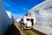Off-road camper at the pass between meter-high walls of snow, East Fjords, Iceland