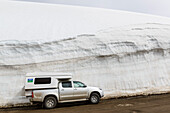 Campers in front of a high wall of snow on a pass over the East Fjords of Iceland