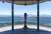 Child looks through telescopic sight, view of the Alps from Pyramidenkogel, Carinthia, Austria