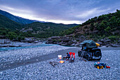Albania, Southern Europe, young couple sitting in front of off-road vehicle with roof tent, campfire, river, Vjosa, Permet