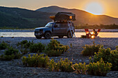 Albania, Southern Europe, young man sits in front of off-road vehicle with roof tent, and enjoys the sunset