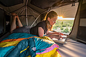 Croatia, Zrmanja, Winnetou, young woman in the evening in the roof tent on an off-road vehicle