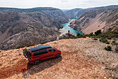 Road trip Croatia, camper on a pitch with a view, two people looking down into the valley