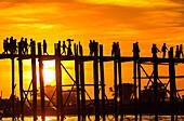 Sunset behind the U Bein Bridge, the longest teak bridge in the world in Myanmar