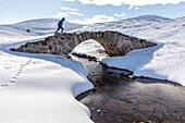 Walkers on stone bridge, Old Miltary Road in snow, Corgarff, Lecht Road, Cairngorms, Highlands, Aberdeenshire, Scotland, UK
