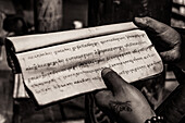 A monk in Tibet holds handwritten text for recitation in a monastery