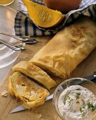 Pumpkin strudel with sheep's cheese; chive quark in bowl