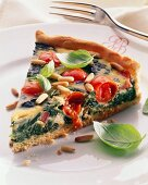 A piece of spinach & tomato quiche with pine nuts & basil