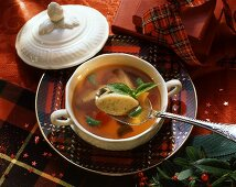 Clear tomato soup with basil dumplings in soup plate
