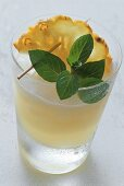 Pineapple drink in glass with pineapple slice and mint