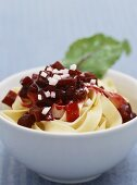 Ribbon noodles with beetroot and goat's cheese in bowl