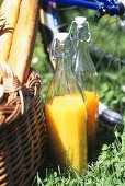 Orange and carrot juice in bottles beside picnic basket