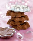 Mini chocolate cakes in a pile with baking tin